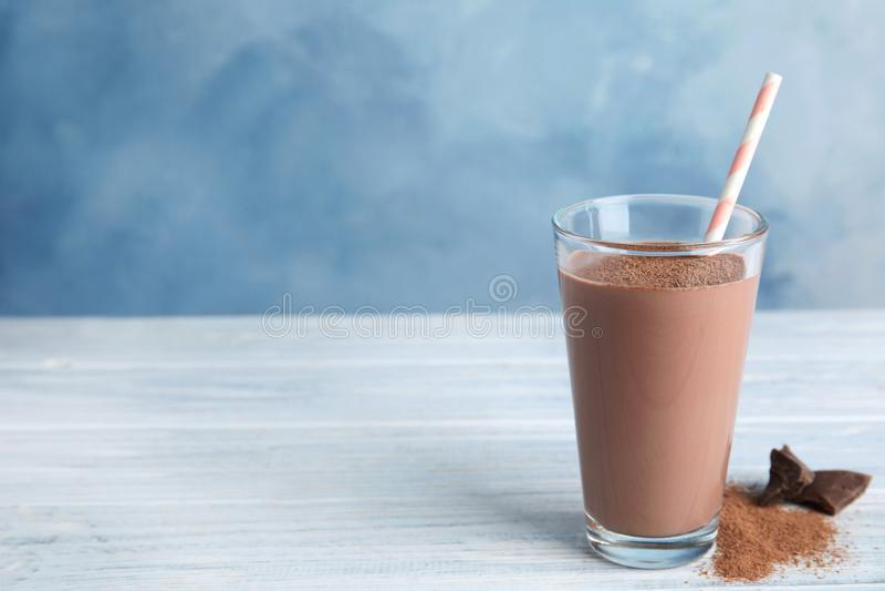 Szkło z smakowitym czekoladowym mlekiem na drewnianym stole, przestrzeń dla teksta zdjęcia royalty free