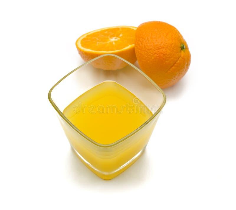 Szkło z sokiem pomarańczowym wśrodku i pomarańcze rozłamem w dwa kawałka fotografia stock