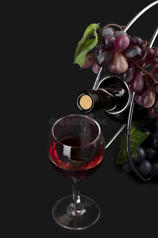 Szkło z winem, butelką i winogradem odizolowywającymi na czerni, fotografia royalty free