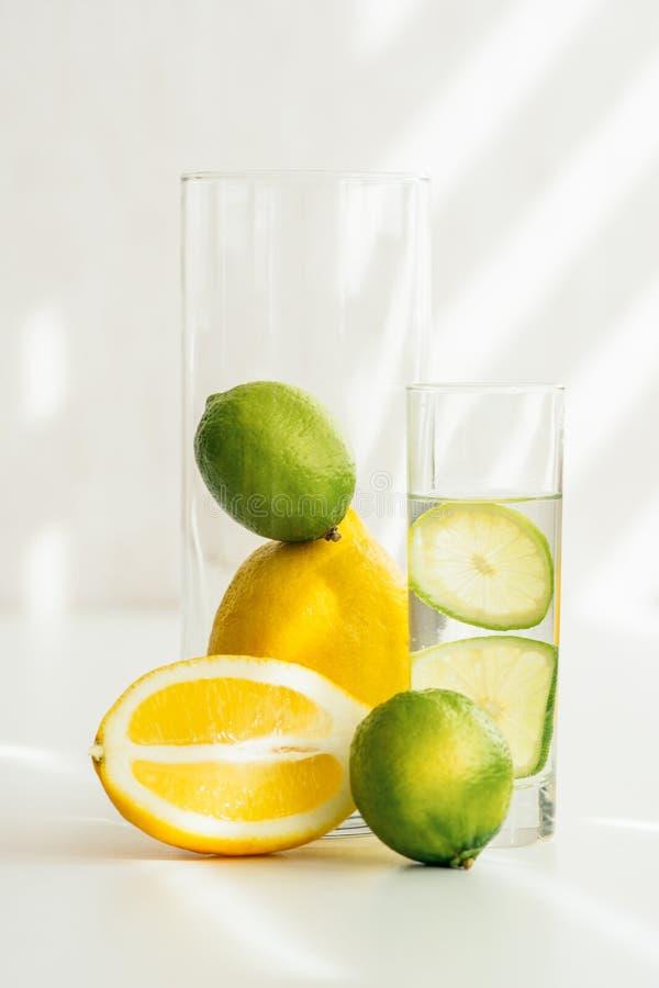 Szkło z wodą, wapno, pomarańcze i wapno w szklanej wazie, zdjęcie stock
