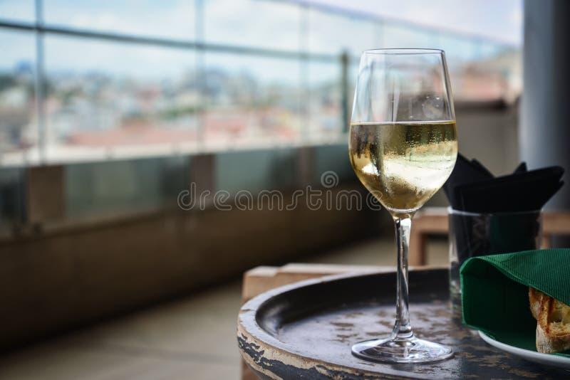 Szkło z zimnym, białym winem na drewnianym stole obraz stock