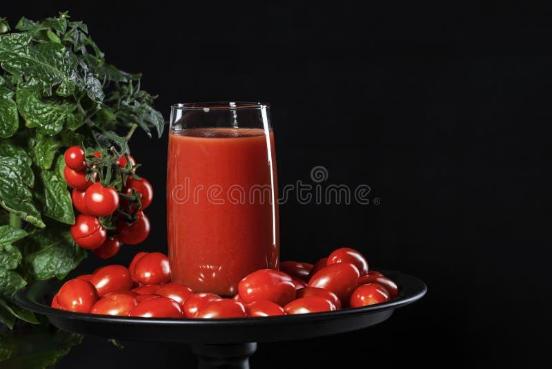 Szkło zakrywający z czereśniowych pomidorów komesami od naturalnego pomidorowego krzaka pomidorowy sok, konceptualny wizerunek obrazy stock
