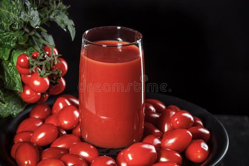 Szkło zakrywający z czereśniowych pomidorów komesami od naturalnego pomidorowego krzaka pomidorowy sok, konceptualny wizerunek obraz stock