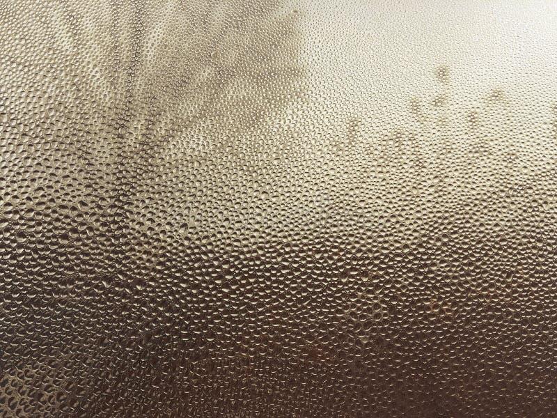 Szkło zakrywający z wodą opuszcza przez, tomowe krople woda na co tonuje drzewna sylwetka, naturalny tło w złocie zdjęcia stock