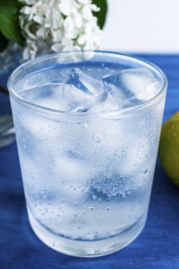 Szkło zimna woda z lodem i cytryną na błękitnym tle obrazy stock