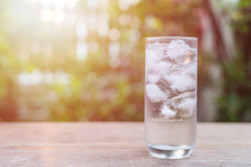 Szkło zimna woda z lodem na stole z plamy natury ogródem obraz stock