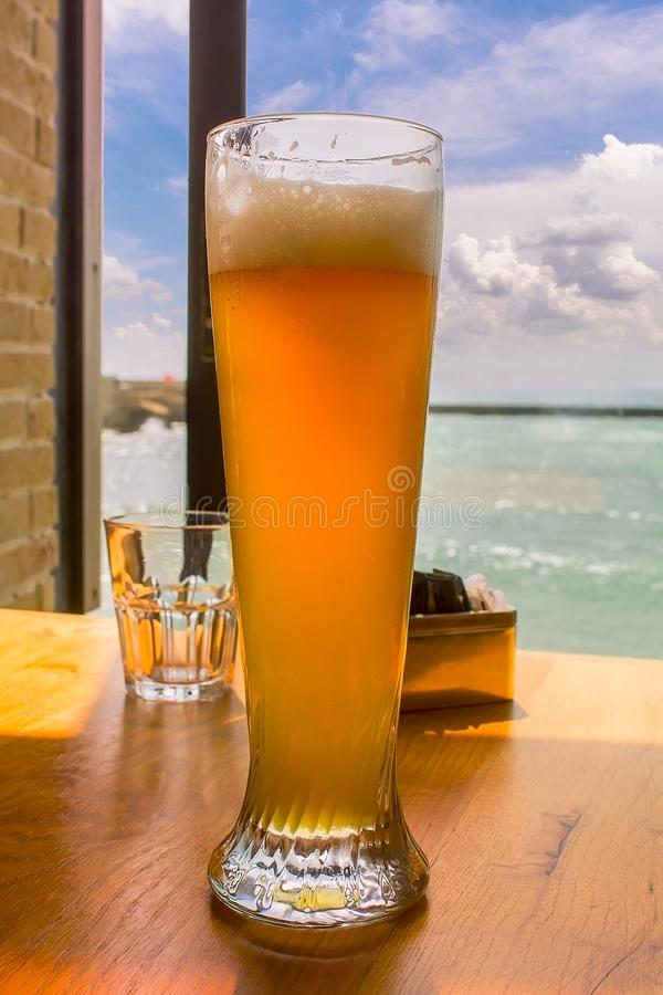 Szkło zimny unfiltered piwo na prętowym stole fotografia royalty free