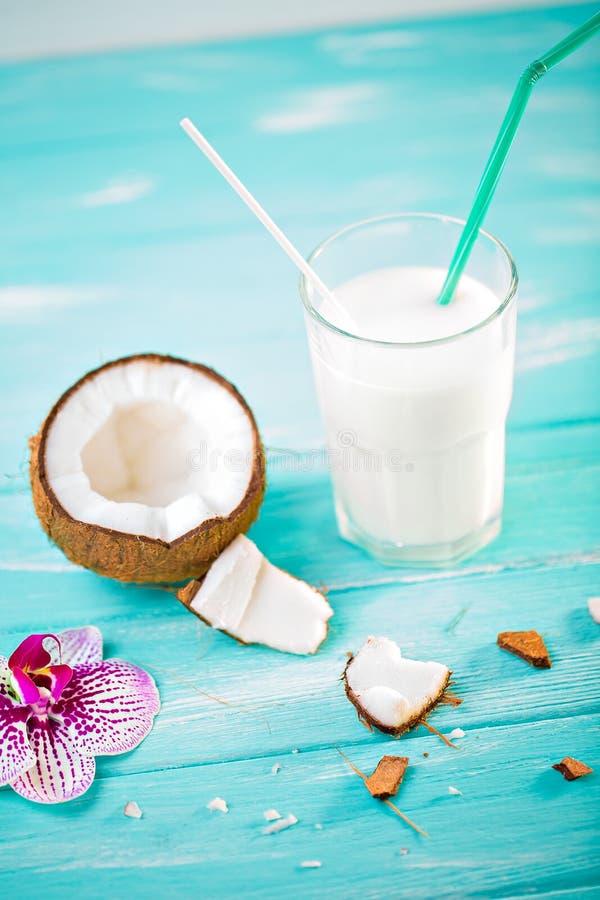 Szk?o kokosowy mleko na b??kitnym drewnianym stole Dekoruj?cy z koksem i menchii orchide? na drewnianym stole Selekcyjna ostro?? zdjęcia royalty free