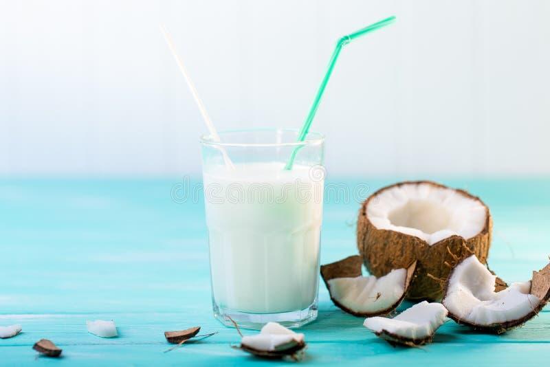 Szk?o kokosowy mleko na b??kitnym drewnianym stole Selekcyjna ostro?? obraz stock