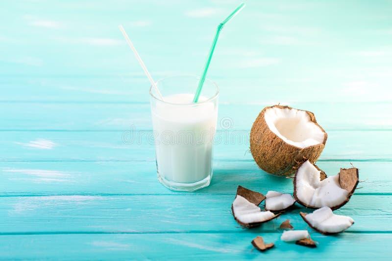 Szk?o kokosowy mleko na b??kitnym drewnianym stole Selekcyjna ostro?? obraz royalty free
