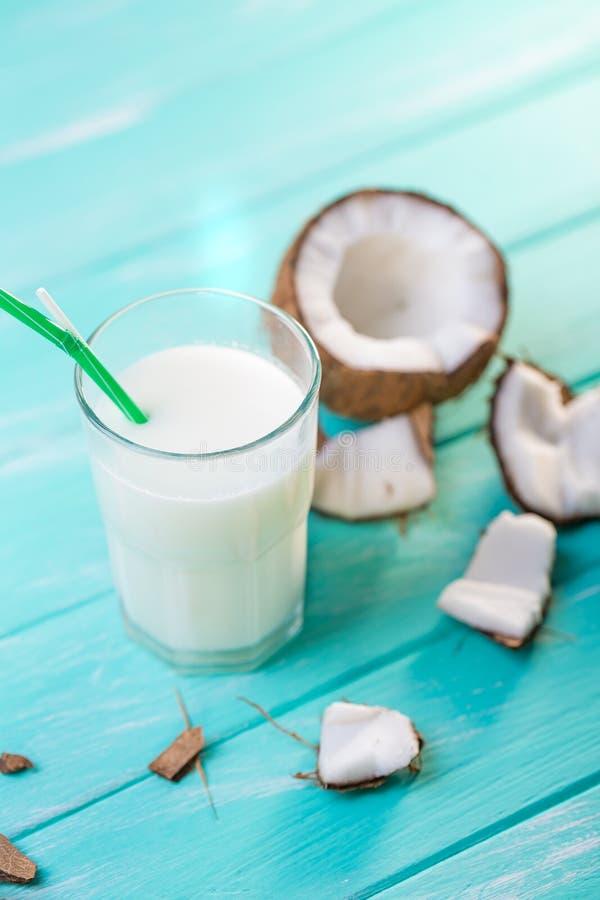 Szk?o kokosowy mleko na b??kitnym drewnianym stole Selekcyjna ostro?? zdjęcie stock