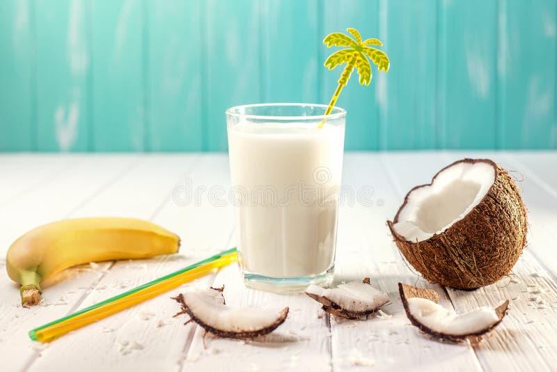 Szk?o kokosowy mleko na bia?ym drewnianym stole, banany tropikalny Selekcyjna ostro?? obrazy royalty free
