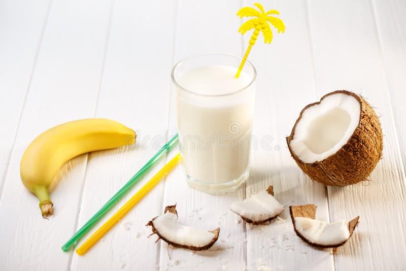 Szk?o kokosowy mleko na bia?ym drewnianym stole, banany tropikalny Selekcyjna ostro?? obrazy stock