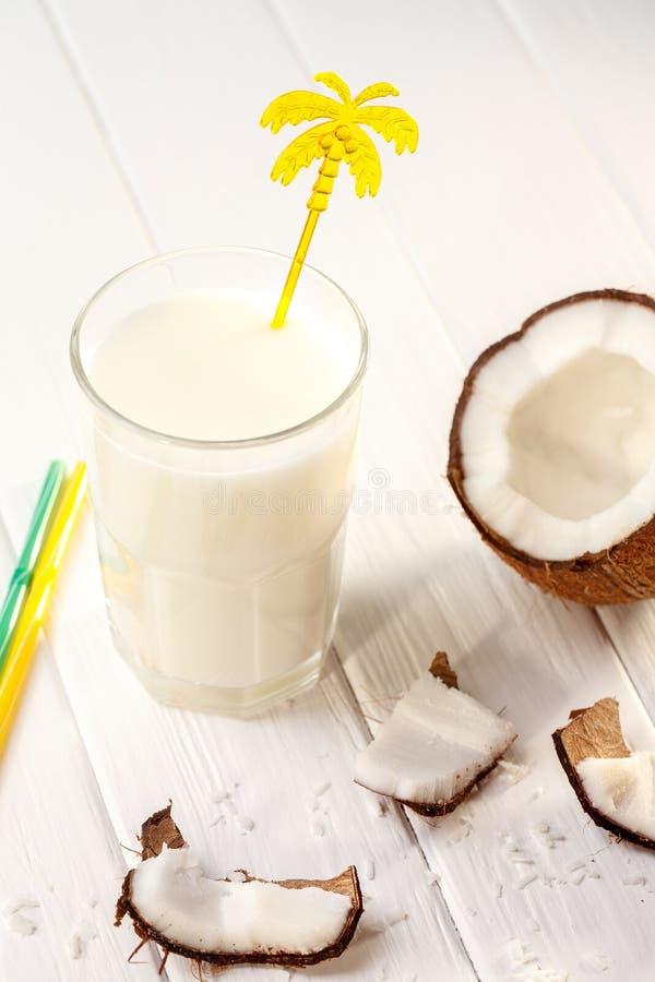 Szk?o kokosowy mleko na bia?ym drewnianym stole, banany tropikalny Selekcyjna ostro?? zdjęcia royalty free