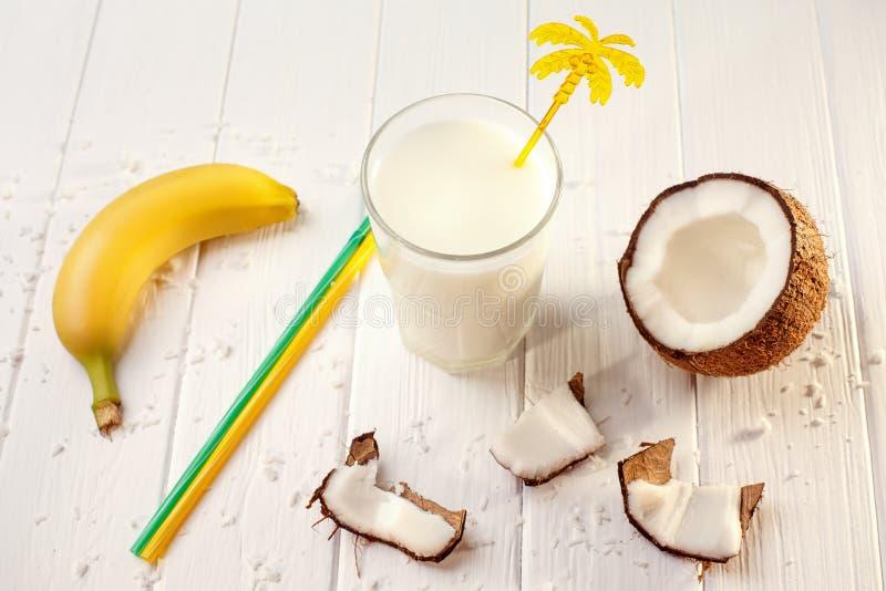 Szk?o kokosowy mleko na bia?ym drewnianym stole, banany tropikalny Selekcyjna ostro?? obraz stock