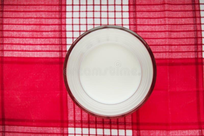 Szk?o mleko stojaki na czerwonym w kratk? p??tnie, odg?rny widok obrazy stock