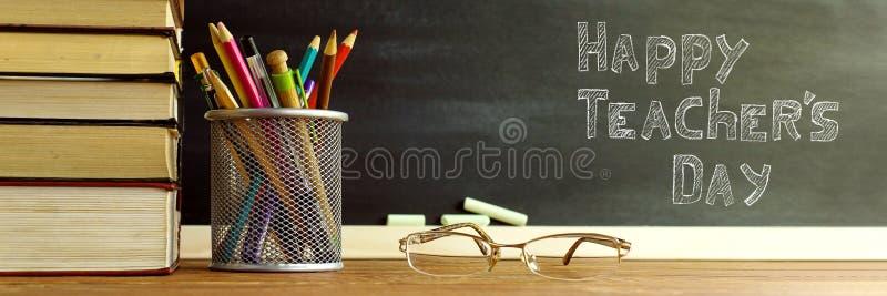 Szk?o nauczyciel rezerwuje i stojak z o??wkami na stole na tle blackboard z kred?, Poj?cie zdjęcie royalty free