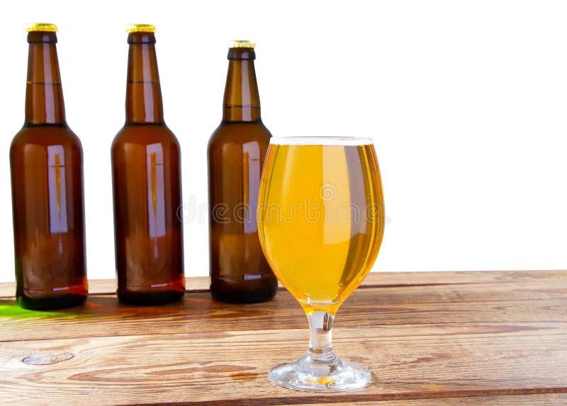 Szk?o piwo i butelki bez logo na drewniany st?? odizolowywaj?cej kopii przestrzeni, szklana butelka obraz stock