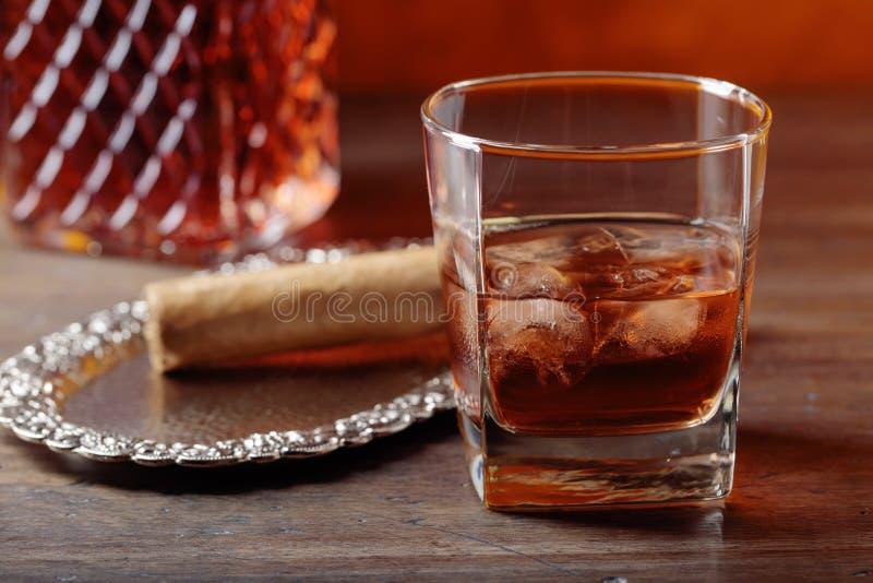 Szk?o whisky i cygaro na starym drewnianym stole zdjęcie stock