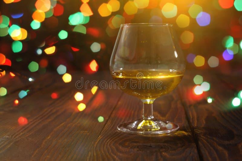 Szk?o whisky lub brandy na drewnianym stole na jaskrawym rozjarzonym tle obraz stock