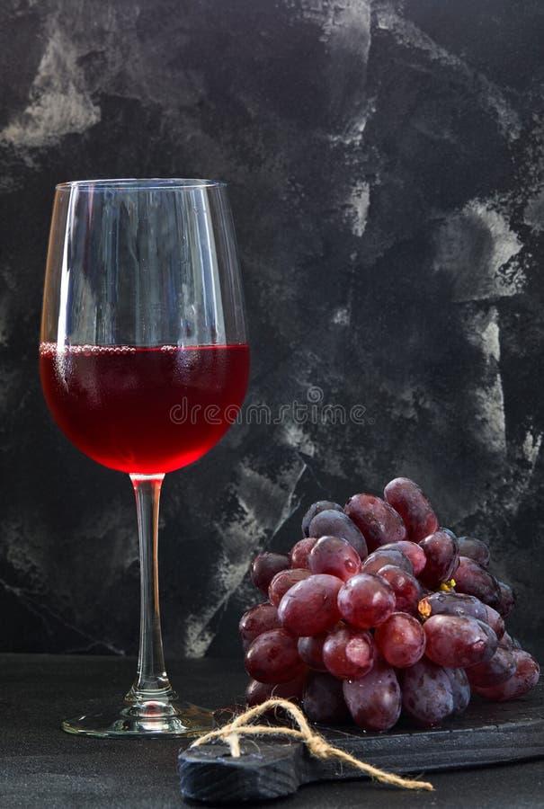 Szk?o wino z winogronami na czarnym drewnianym stojaku zdjęcie stock