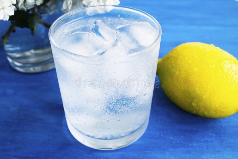 Szk?o zimna woda z lodem i cytryn? na b??kitnym tle fotografia royalty free