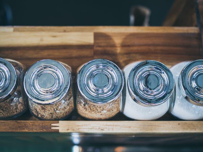 Szklana butelka brązu cukier i biały cukier na drewnianej półce w cukiernianym odgórnym widoku obraz stock