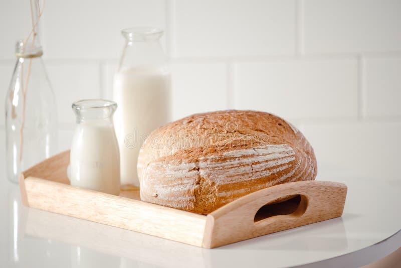 Szklana butelka mleko z chlebem na drewnianej tacy odizolowywającej na białym tle dla karmowego i zdrowego pojęcia Z kopii przest zdjęcia royalty free