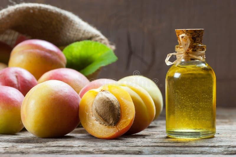 Szklana butelka moreli ziarna nasiona oleju prunus armeniaca oleum z świeżymi dojrzałymi morelowymi owoc zdjęcia stock