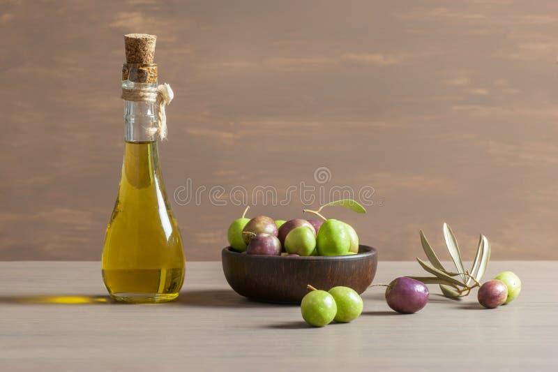 Szklana butelka oliwa z oliwek i drewniany śniadaniowy puchar z surowymi tureckimi oliwek ziarnami, liśćmi na drewnianym nieocios zdjęcie stock