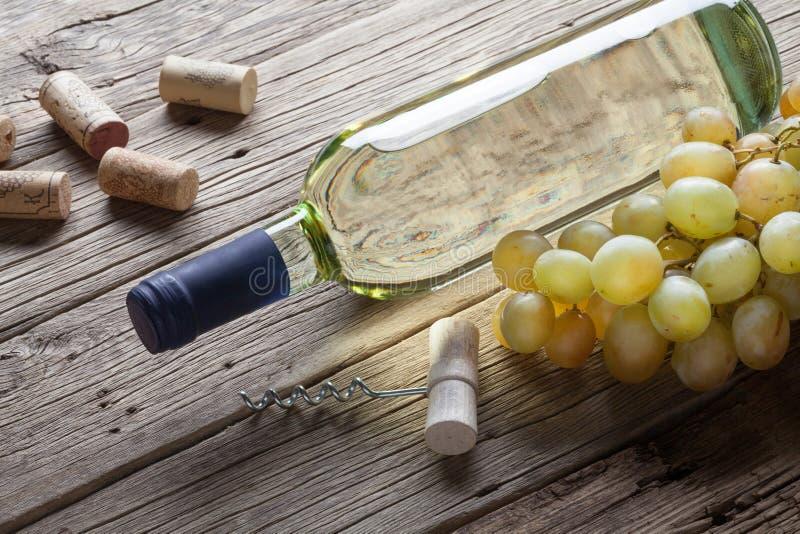 Szklana butelka wino z corkscrew na drewnianym stołowym tle zdjęcie royalty free