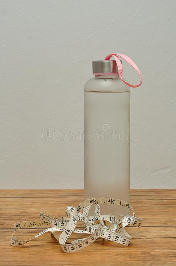 Szklana butelka wypełniał z lodem zimna woda i pomiarowa taśma - zdjęcia royalty free