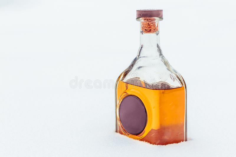 Szklana butelka z elita alkoholem i wosk foką w śniegu obraz royalty free