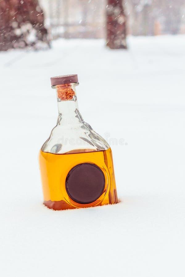 Szklana butelka z elita alkoholem i wosk foką w śniegu obraz stock