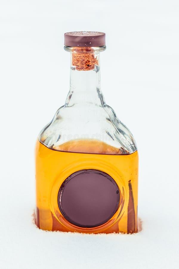Szklana butelka z elita alkoholem i wosk foką w śniegu obrazy royalty free