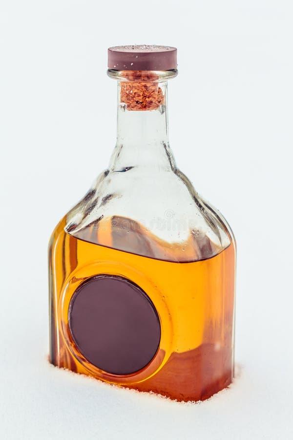 Szklana butelka z elita alkoholem i wosk foką w śniegu Luksusowy ciężki napój zanieczyszczenie na rzecznym Arno zdjęcie stock