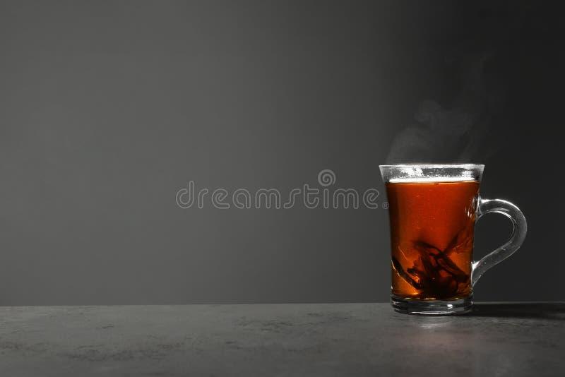 Szklana filiżanka gorącej herbaty liściastej na stole na szarym tle obraz royalty free