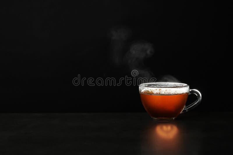 Szklana filiżanka gorÄ…cej herbaty na stole na czarnym tle zdjęcia stock
