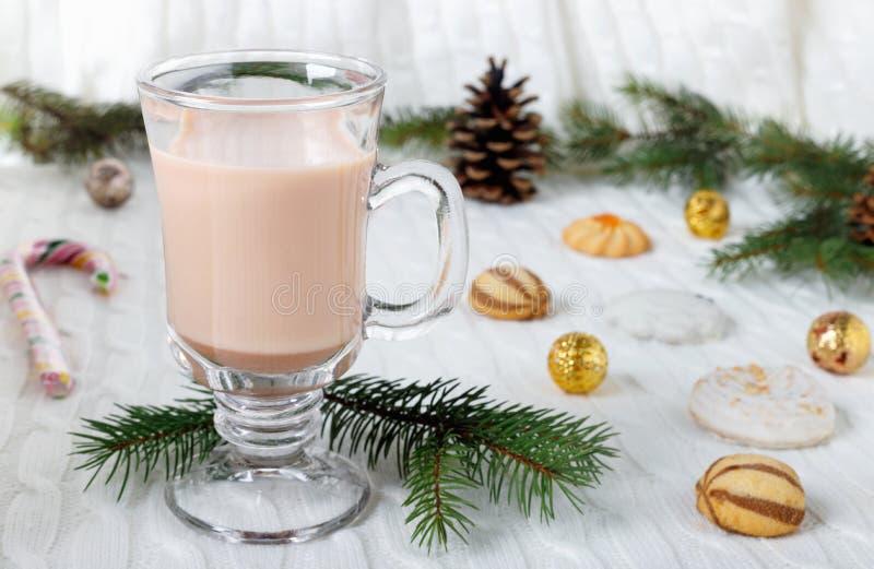 Szklana filiżanka gorący kakao z mlekiem, cukierkami i słomianą tubką na tle, fotografia royalty free