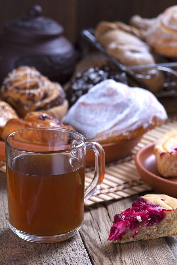 Szklana filiżanka herbata, rolki z maczkiem w drewnianej koszykowej szklanej filiżance herbata i rolki z maczkiem obraz stock