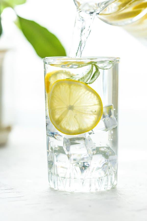 Szklana filiżanka i karafka woda, lód, mennica i cytryna na białym stole, obrazy stock