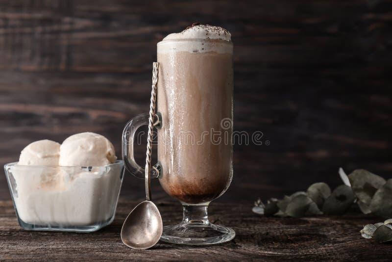 Szklana filiżanka z zimną kawą i lody na drewnianym stole zdjęcia stock