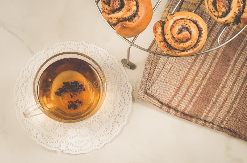 szklana herbata, rolka z maczkiem na kratownicie dla piec i rolka z maczkiem na kratownicie dla piec na a/śniadanie z szklaną her obrazy royalty free
