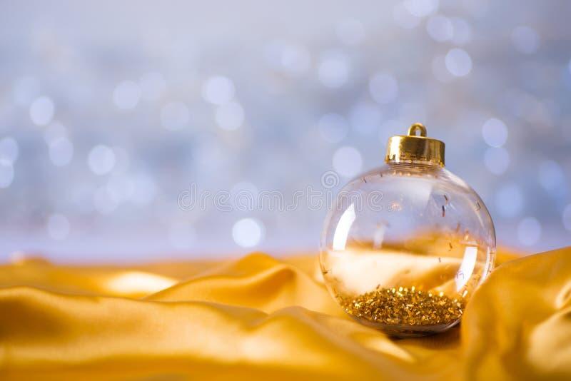 Szklana przejrzysta Bożenarodzeniowa piłka z złocistym świecidełkiem na wśrodku złotej atłasowej tkaniny na lekkim bokeh tle fotografia royalty free