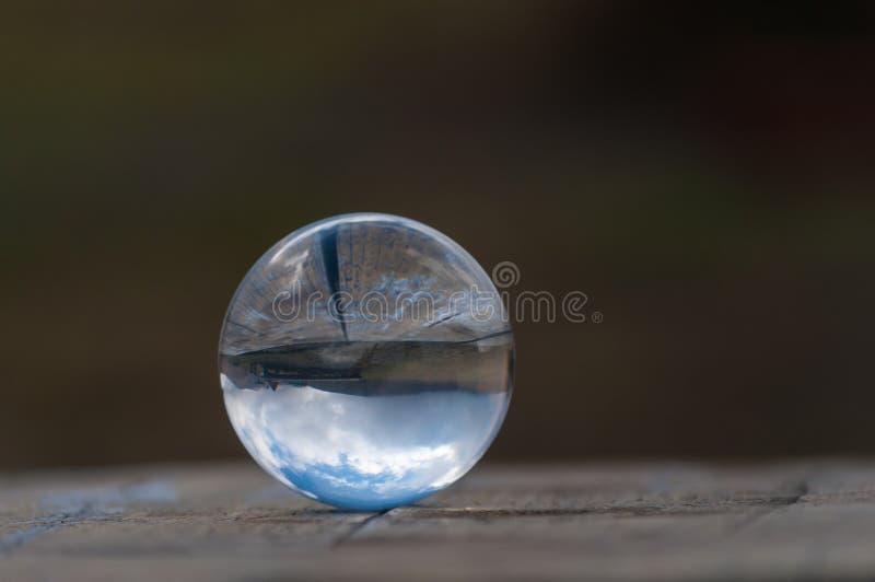 Szklana przejrzysta krystaliczna szklana piłka na ciemnozielonym fotografia stock