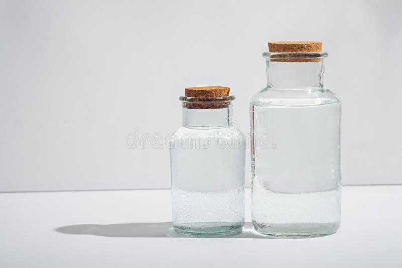 Szklane butelki z korkowymi deklami na białym tle, boczny widok obrazy stock