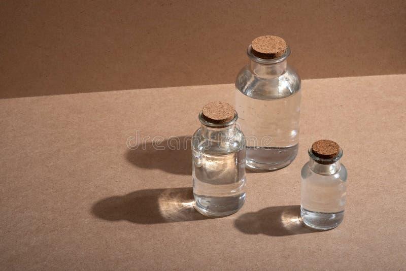 Szklane butelki z korkowymi nakrętkami przeciw tłu oznakuję drewniany lub kartonowy fotografia stock