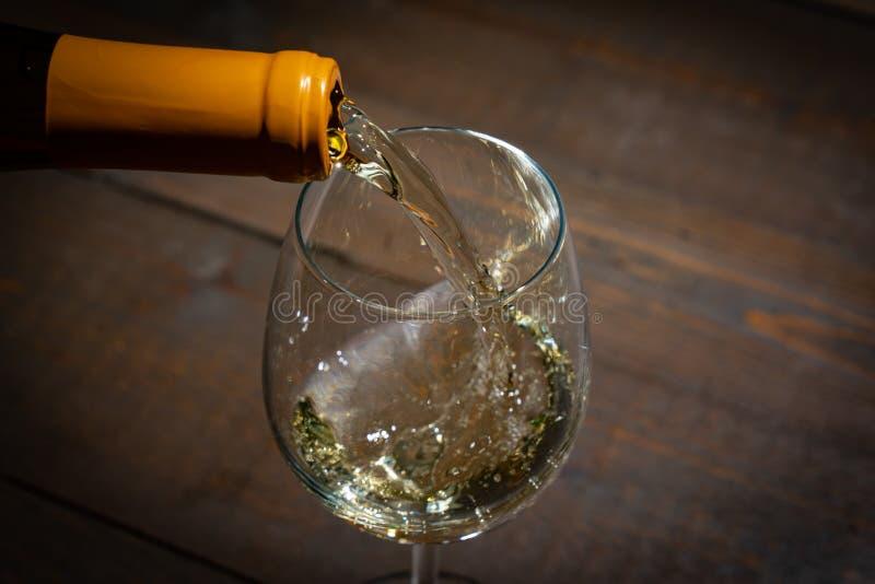 szklanego dolewania biały wino fotografia stock