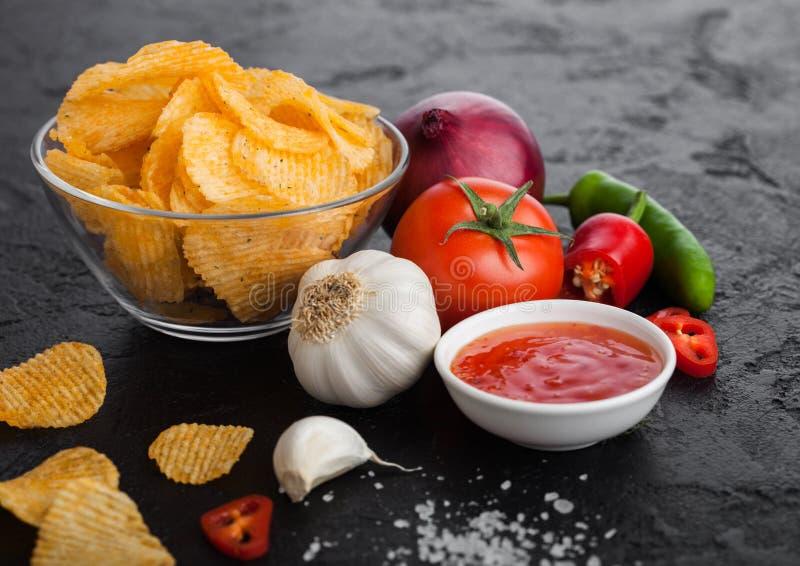 Szklanego pucharu talerz z kartoflanych chipsów układami scalonymi z papryką i chili pieprze na czerń kamieniu zgłaszamy tł zdjęcia stock