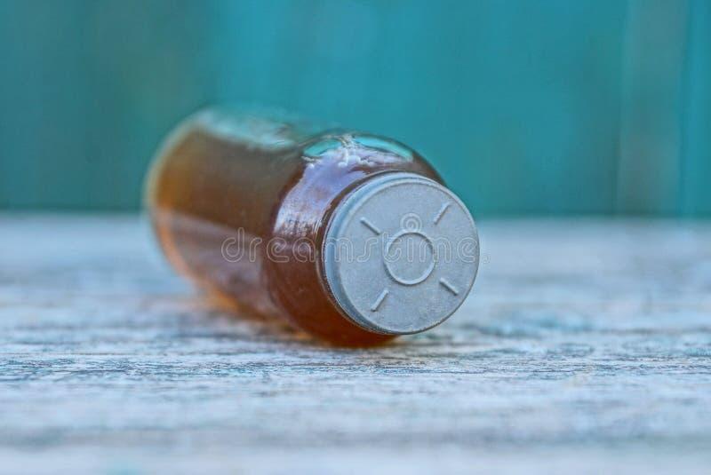 Szklanej butelki ampułka z brąz medycyną na szarym stole na zielonym tle obraz stock